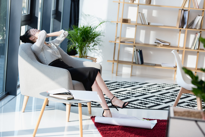 tired businesswoman relaxing with hands on face while sitting on sofa at office