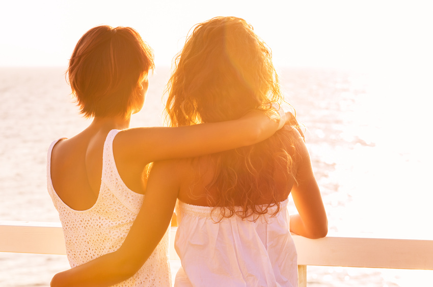 Rear View Of Two Young Women Looking At Sea At Sunset