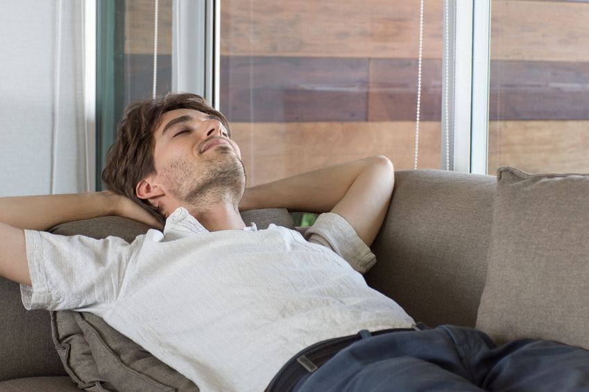 Image of a man concentrating on his breathing and meditating on the sofa