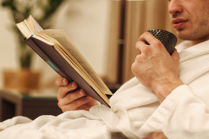 Cropped shot of a man drinking tea reading book relaxing at his hotel room copyspace beverage recreation hobby leisure lifestyle reader knowledge relaxation smart holidays weekend enjoyment peace calm