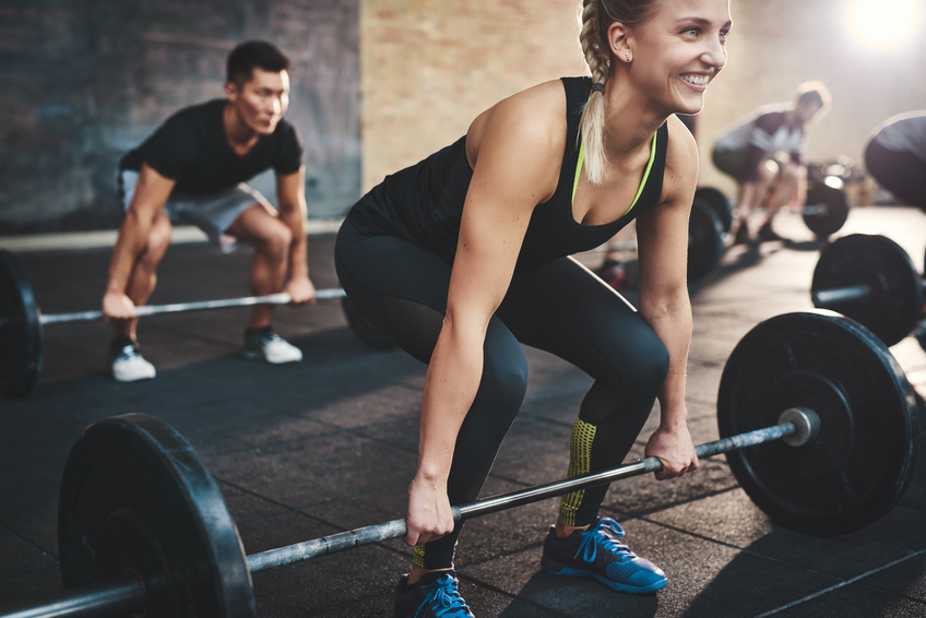 Cheerful muscular young woman with ponytail and black tights performing dead lift barbell exercises with other students