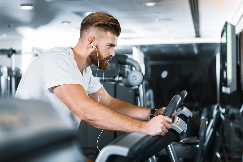Busy sportsman is at exercise bike with earphones, he looking ahead