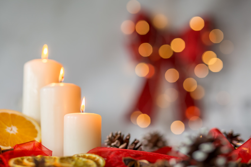 Close-up of white candles and orange as christmas time decoration