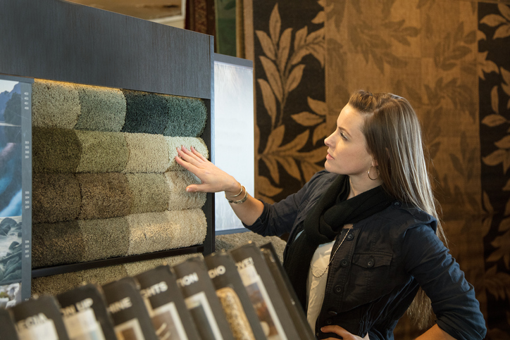 Woman shopping for carpeting and flooring in a home interiors store.