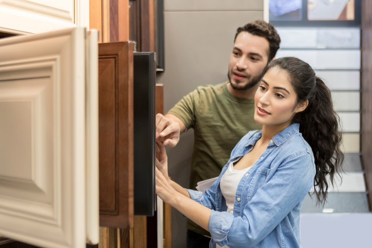 Excited young couple look at cabinet samples for their new home. She are examining the different types of cabinets. They are opening and closing the sample cabinets.