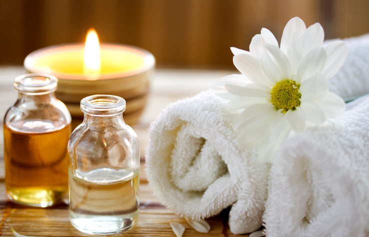 """Essential oil bottles, towels, candle and flower in health spa for spa treatment."""