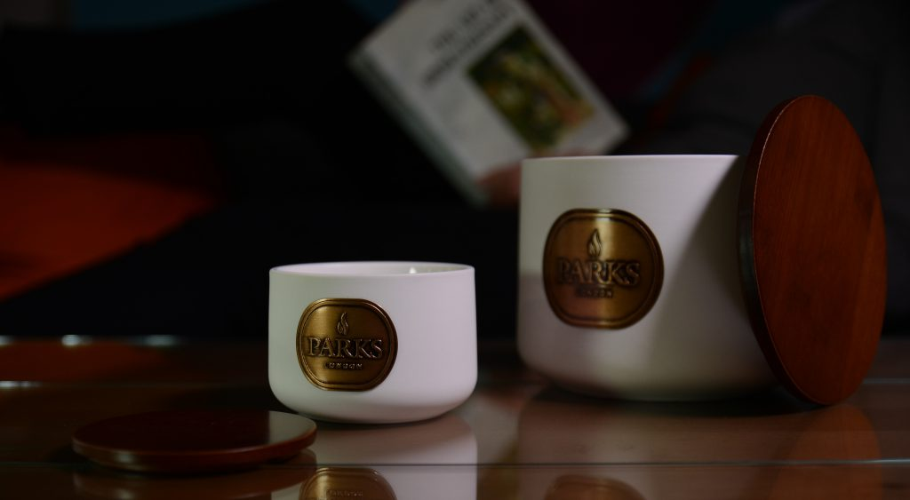 Royal Neroli Ceramic 1 wick and three wick candles with man reading in the background