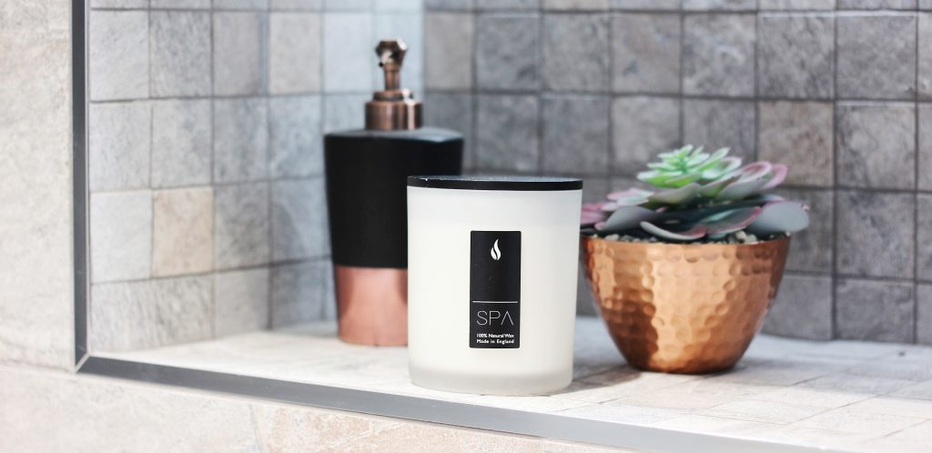 spa candle on shelf with soap and plant