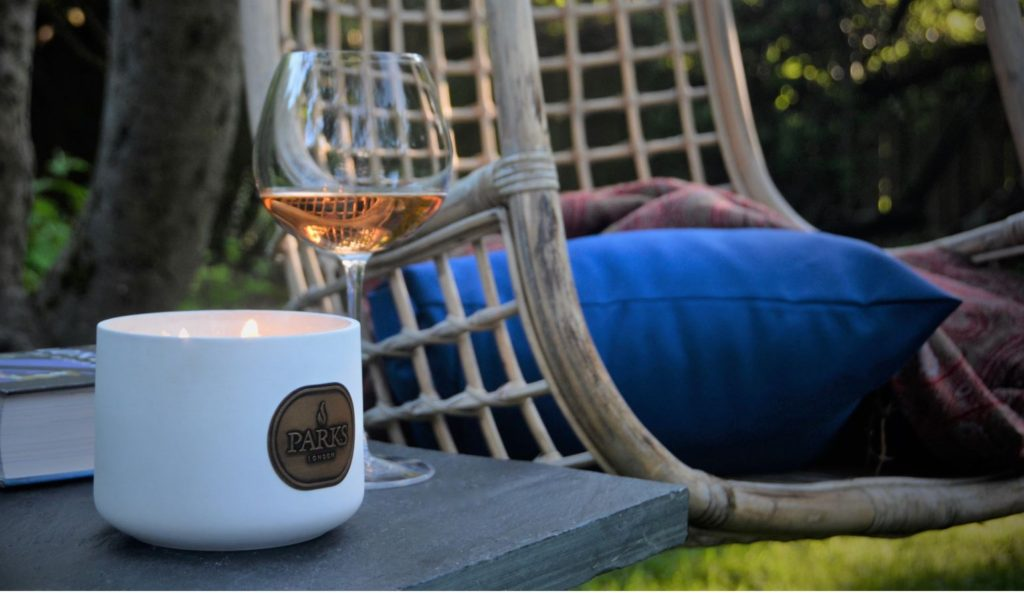 Ceramic scented candle in garden with Glass of Wine